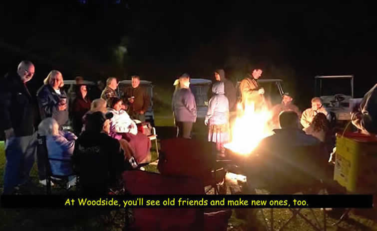 Color photo of men and women standing around campfire at night.